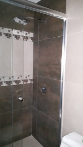 "Ceramic tile walls & floor; large glass shower with ""rainforest"" shower head"
